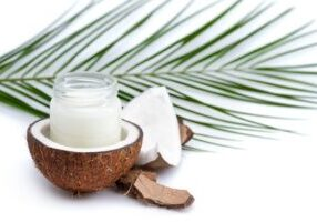 ripe coconut and organic coconut oil in glass jar with coconut leaf isolated on white